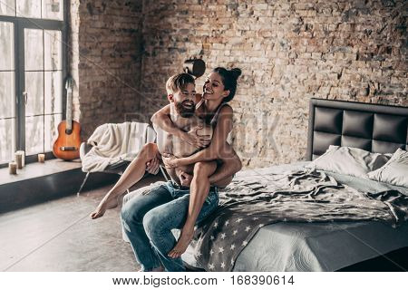 Happy couple. Beautiful young couple having fun in bedroom at home while shirtless man giving his girlfriend piggy back ride