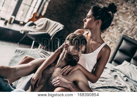 True love. Handsome young bearded man sitting on the floor while beautiful girl keeping arms around him
