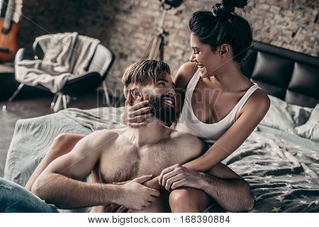 Falling in love. Beautiful young couple smiling and looking at each other while resting at home