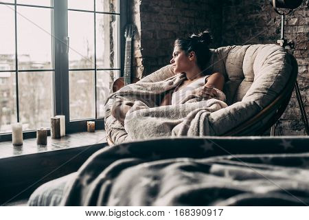 Lazy day at home. Beautiful young woman covered with blanket looking through window while sitting in big comfortable chair at home