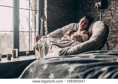 Time to rest. Attractive young woman covered with blanket sleeping and smiling while sitting in an armchair at home
