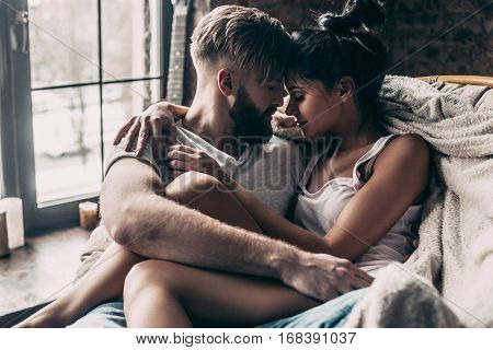 Love is in the air. Young couple sitting face to face and keeping eyes closed while spending time at home together