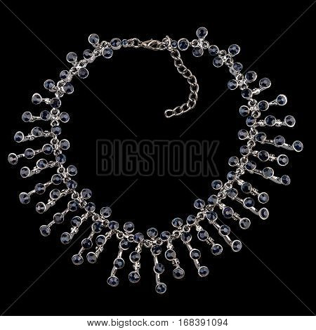 Golden necklace with sapphire and diamonds on black background