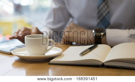 Using moment to make some notes. Confident mature man writing something in his note pad while sitting at the table outdoors with cafe in the background