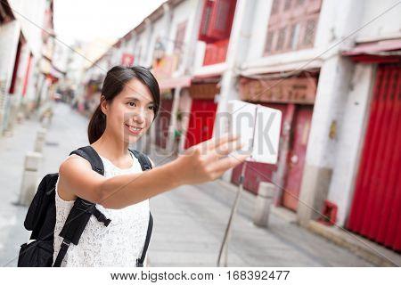 Woman using digital camera to take selfie