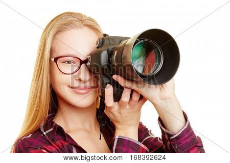 Young woman with glasses as photographer taking pictures with digital camera