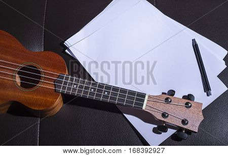 Ukulele and Blank Music Paper Notes on Brown Leather Sofa.