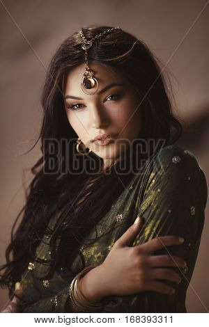 Portrait of young woman with luxury makeup. Beautiful girl with stylish hairstyle agaist desert background, young lady wearing fashionable golden jewelry and dress. Beauty salon consept. Mixed race Asian Caucasian female model looking at camera.