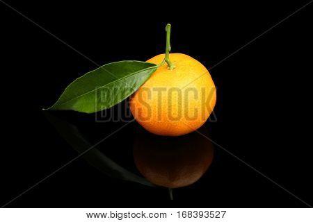 Fresh mandarin with leaf on black background