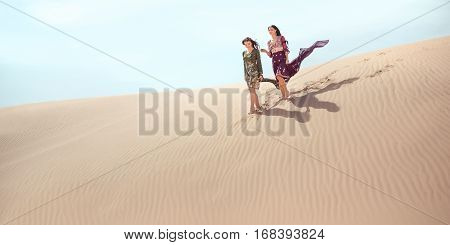 Adventure of two sisters princesses happy walking in the desert and happy laughing. Two beautiful mixed race asian caucasianl girls enjoy a joint journey. Creative art fashion shot of two gorgeous attractive models outdoors in arabian indi