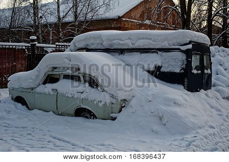 The snowdrift covers cars. Old cars after a snowfall.