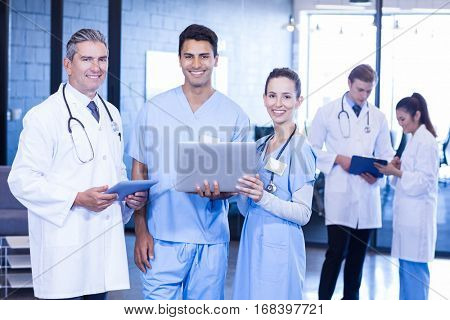 Portrait of doctors smiling while using laptop and digital tablet in hospital