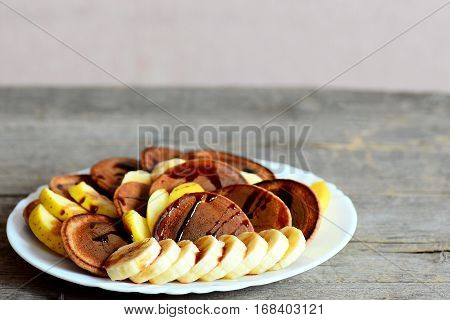 Chocolate pancakes with bananas, apples and caramel sauce on a white plate isolated on wooden background with copy space for text. Pancake day food for children, family