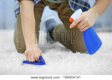 Young man cleaning carpet at home, close up