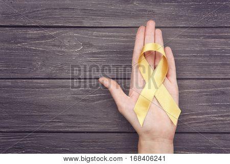 Female hand holding golden ribbon on grey wooden background. Children cancer concept
