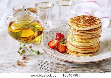 Pancakes with strawberries and herbal tea in transparent teapot