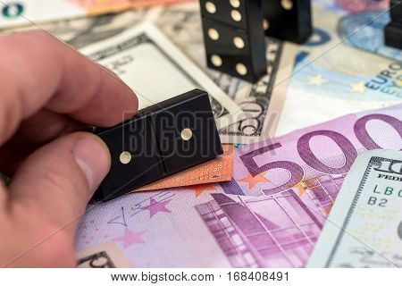 Finger pushing domino standing on euro and dollar cash.