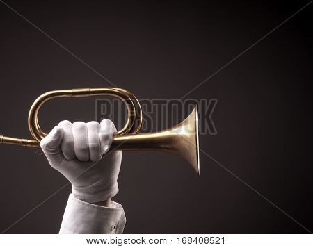 Hand with white gloves holding an old dusty trumpet on a dark background
