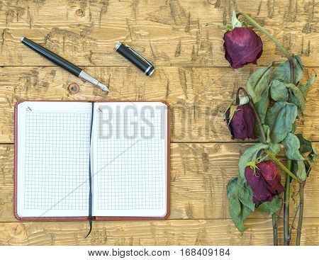 Wilted roses with a notebook and fountain pen on a rustic table. Concept of holiday memories. Top view.