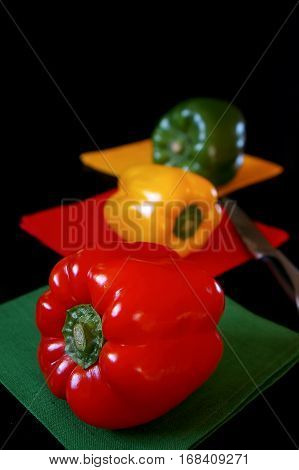 Tri-color bell peppers: red yellow green on black background. Focus selective