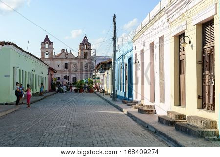 Camaguey Cuba - 11 January 2016: People walking in front of the Carmen church on colonial Camaguey Cuba