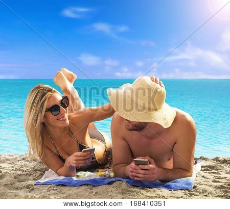 happy young couple lying holding cell phones on a tropical beach