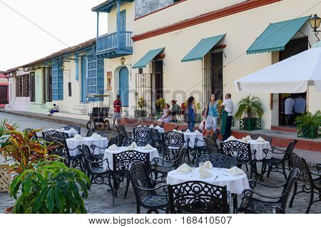 Camaguey Cuba - 11 January 2016: People walking in front of a restaurant in colonial houses of Camaguey Cuba