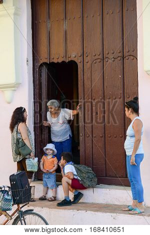 Camaguey Cuba - 11 January 2016: People speaking in front of a entrance door in colonial house at Camaguey Cuba
