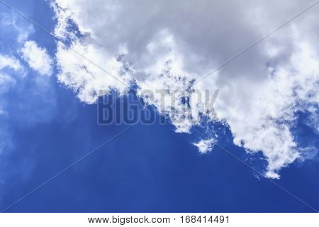 Blue sky background with white clouds and rain clouds. The vast blue sky and clouds sky on sunny day. White fluffy clouds in the blue sky.