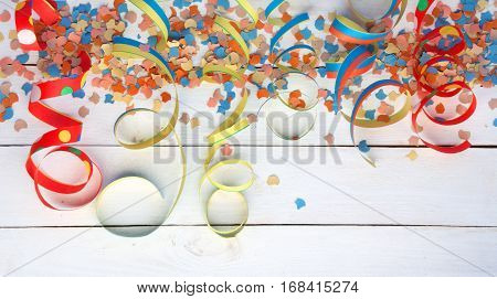 Colorful air streamers and confetti on white wooden boards for carnival and party