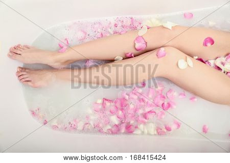 Woman relaxing in bath with foam and petals, closeup of female legs
