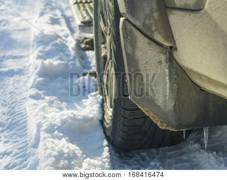 A rear of a vehicle with icicles on the splash guard outdoor cropped shot concept of the seasons change