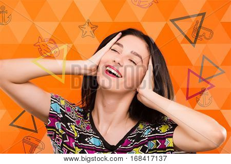 Beautiful smiling young woman, with straight dark hair, wearing on colorful shirt, posing on the orange geometric background with colorful triangles and sea set anchor, starfish, dive mask icons, in studio, waist up
