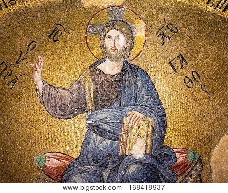 Byzantine Mosaic of Christ pantocrator sitting on a throne, making a blessing sign with his right hand, holding a book in his left, Pammakaristos church in Istanbul, Turkey - October 11, 2013