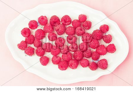 Fresh and delicious raspberries in a white plate