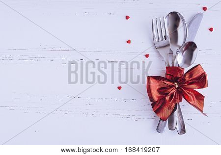 Valentine's Day tabble setting with cutlery on white shabby chic background. Valentine's Day place setting cutlery on white wooden background. Romantic love Valentines concept. Copy space. Top view. poster