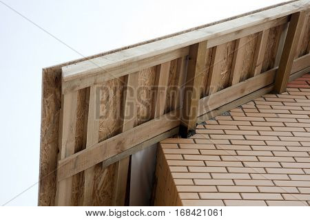 Angle Wall and Roof of the house with exposed wooden beams on the background of blue sky.