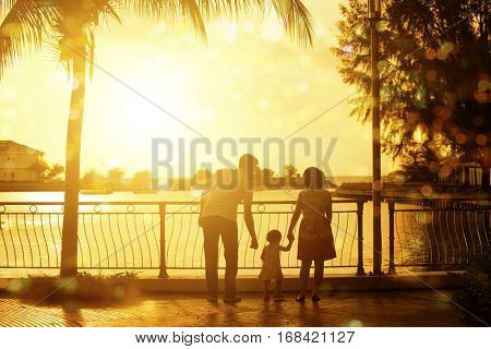 Rear view silhouette of young family enjoying outdoor activity together, walking in beautiful sunset during holiday vacation.
