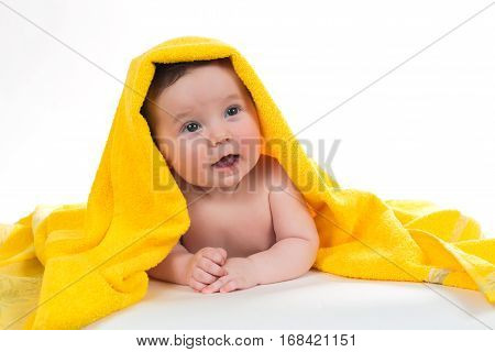 Newborn baby lying down and smiling in a yellow towel.