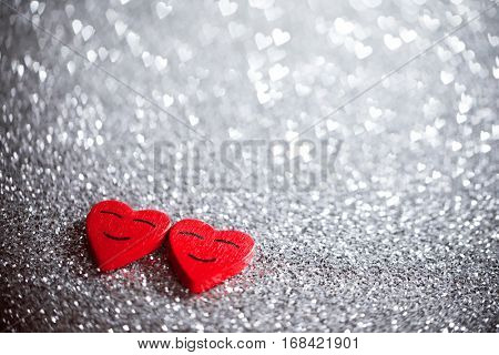 Two smiling red hearts on silver glitter background, relationship valentines day concept