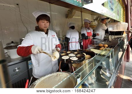 SHANGHAI CHINA - MARCH 26: Unidentified Chinese people trades traditional food on March 26 2016 in Shanghai China. Shanghai is the largest Chinese city by population.