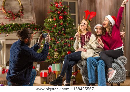 Group of happy young people photographing at christmastime