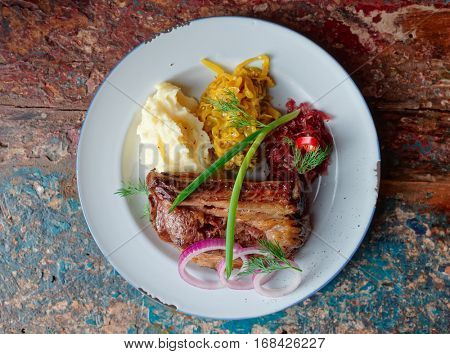 Grilled pork ribs with sauerkraut and mashed potatoes on restaurant table