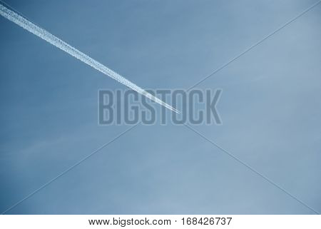One plane leaves contrails trace in a clear blue sky