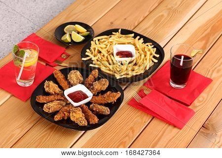 potatoes and wings with sauce in the plate on the table.