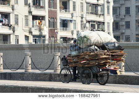 SHANGHAI CHINA - MARCH 26: Cargo-carrying Rickshaw tricycle at the street on March 26 2016 in Shanghai China. Shanghai is the largest Chinese city by population.