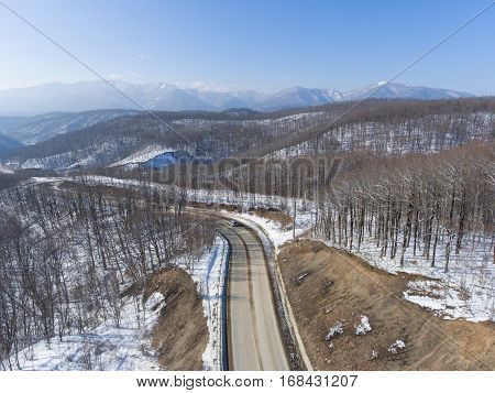 Aerial view of winter mountain road in the woods.