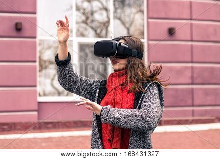 virtual reality headset VR glasses VR goggles - beautiful young girl with virtual reality headset or 3d glasses posing on the street interested by 360 image