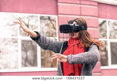 virtual reality headset VR glasses VR goggles - beautiful young girl playing with virtual reality headset or 3d glasses on the street interested by 360 image