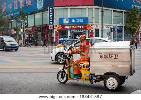 Beijing, China - Oct 30, 2016: Roadside cleaner on bike traverse a major intersection at the 700-year-old Wangfujing Street and Dengshikou West Street. Chinese characters on cart mean